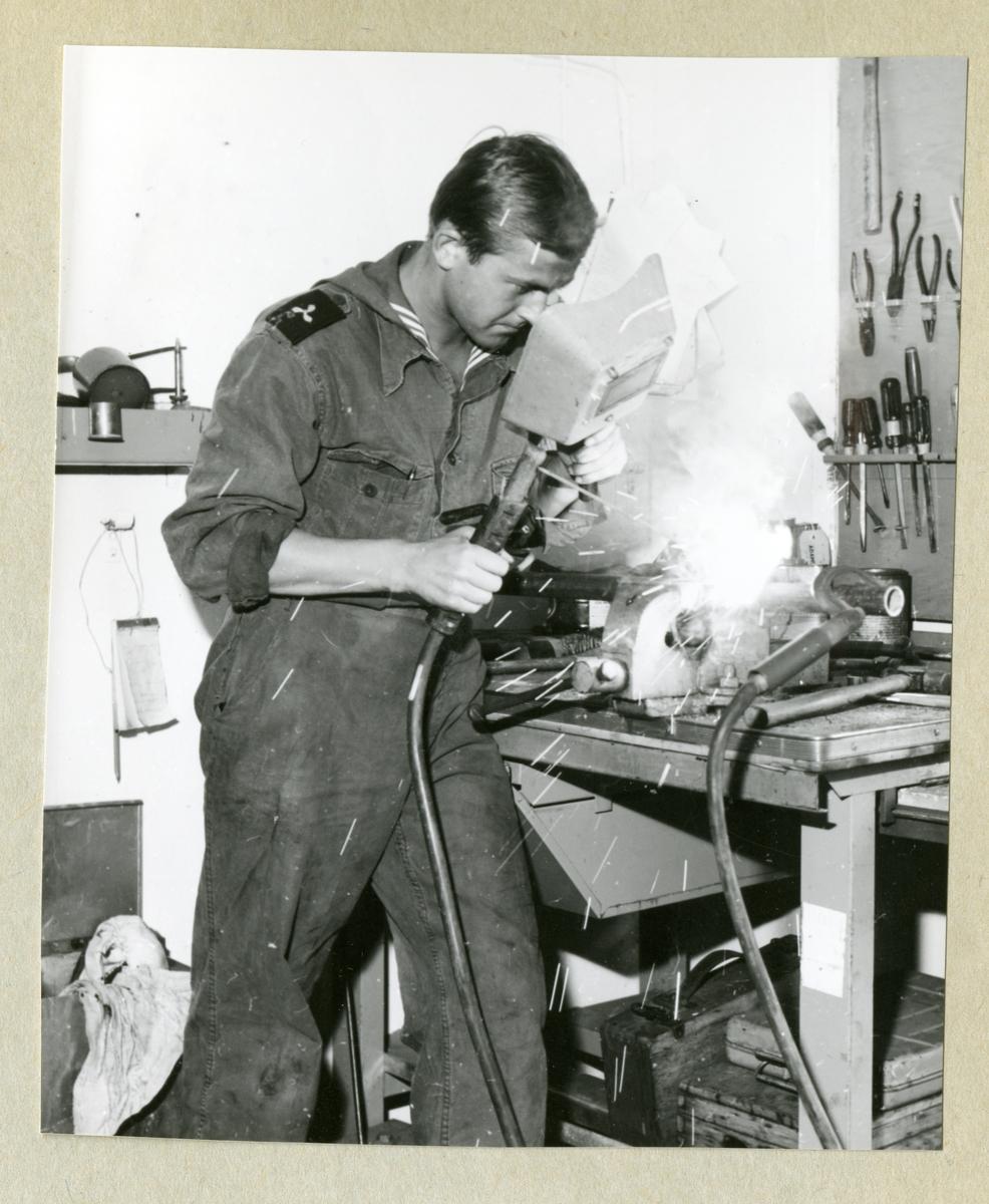 Bilden föreställer en besättningsman som arbetar med att svetsa. Bilden är tagen i samband med minfartyget Älvsnabbens långresa 1966-1967.