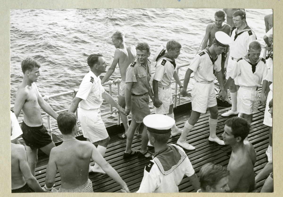 Bilden föreställer besättningsmän i sommaruniform dansa ringdans ombord på minfartyget Älvsnabbens däck under en julhelg. Bilden är tagen i samband med långresan 1966-1967.