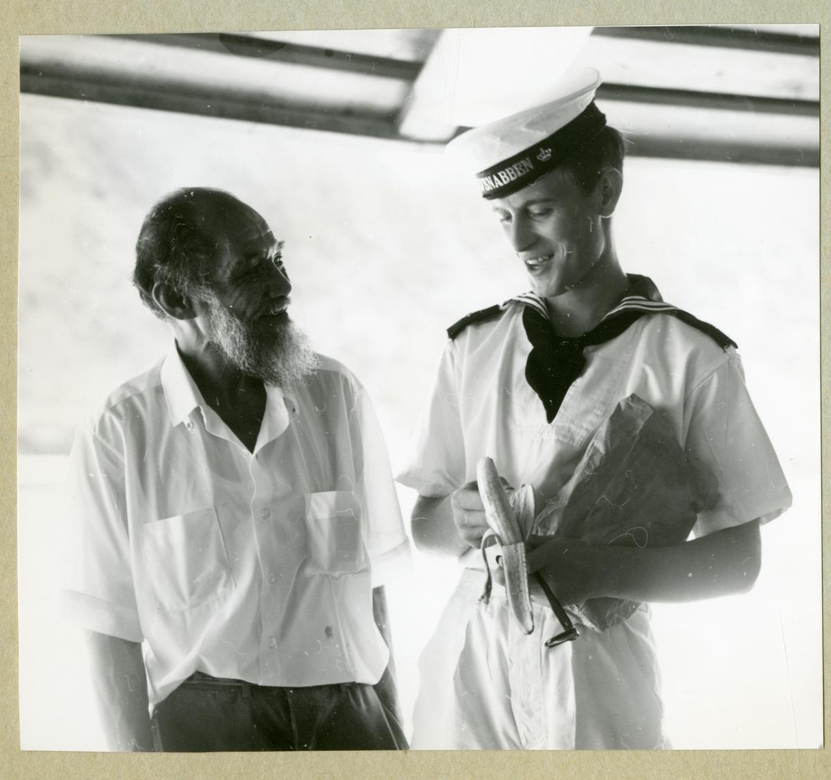 Bilden föreställer en besättningman i vit uniform som skalar en banan. Bredvid står en äldre man. Bilden är tagen under minfartyget Älvsnabbens långresa 1966-1967.