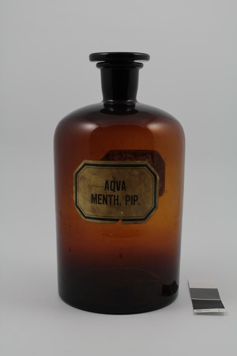 Brun smalhalset glasskrukke med glasspropp. Til flytende væske. 5 liter. Hvit etikettmed sort skrift og kant.   Aqua menthane pip. Peppermyntevann laget på apoteket, brukes i munnvann og andre oppløsninger. 511546 betyr: produsert i 1975 (5) november (11), produksjonsnr. 46. På labben (5).