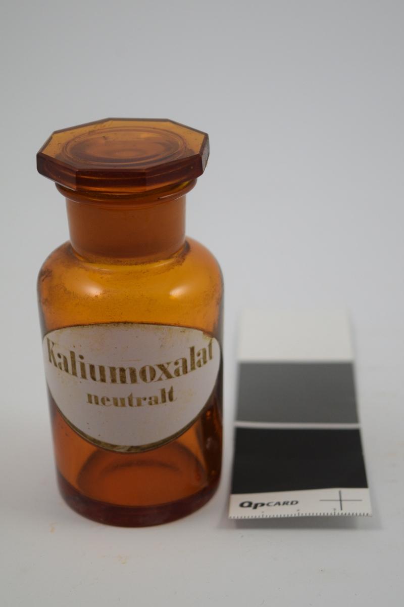 Brun glasskrukke med glasspropp. Etikett hvit med sort skrift. Kaliumoxalat - til bruk i legemiddelproduksjon.