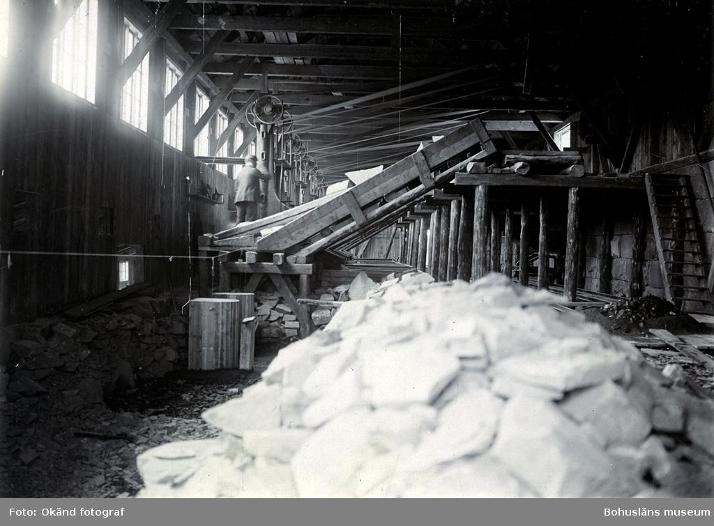 """""""Rixö stenhuggerier, (interiör av fabriken för maskinhuggning av smågatsten), den 29 aug. 1906, då Tekniska Samfundet i Göteborg, besökte Rixön, på inbjudan av Skandinaviska Granit Aktiebolaget, Halmstad.""""(enligt notering på kortets baksida)"""