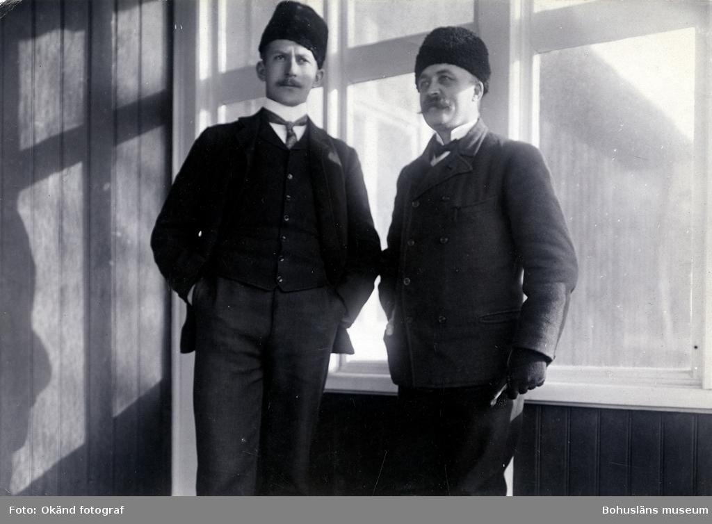 Två män i pälsmössa och kostym står framför ett fönster