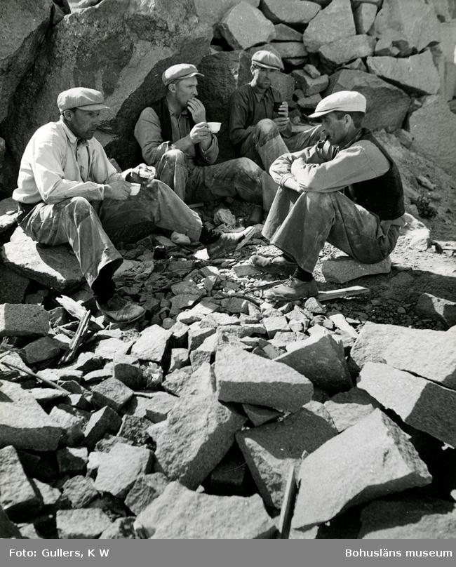Fyra stenhuggare sitter i ett stenbrott och dricker kaffe