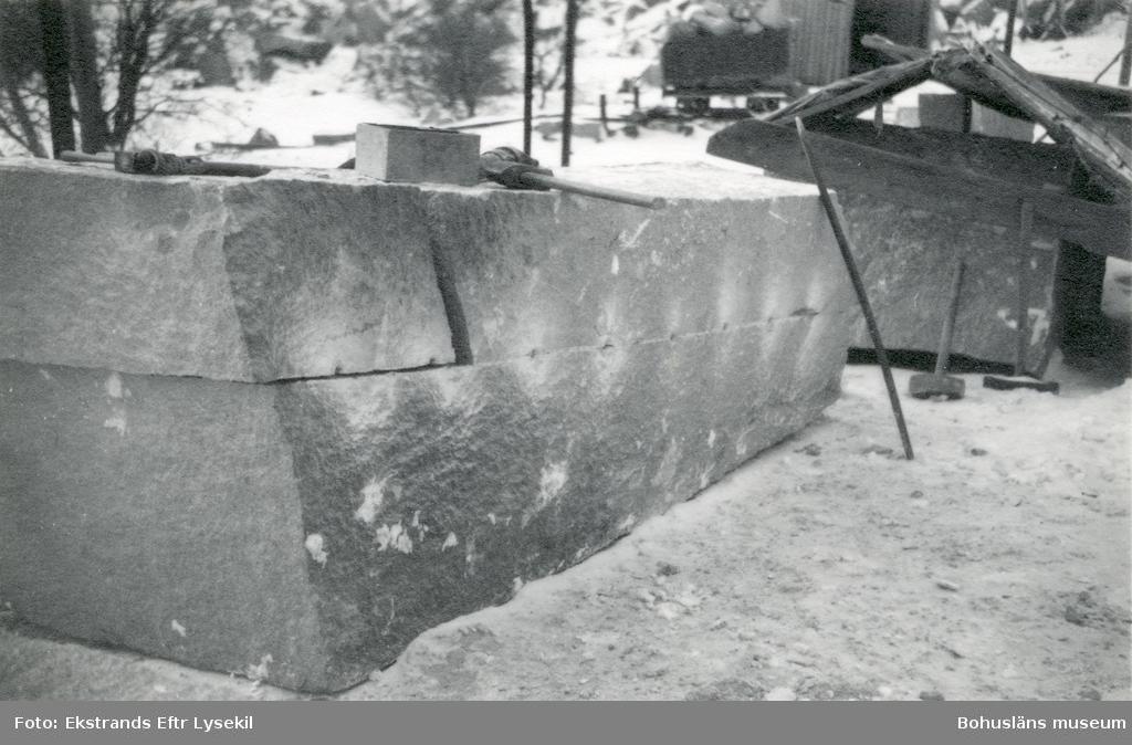 Verktyg och stenblock, blocket har en borrsöm varefter man klyft blocket i två, den övre halvan har i sin tur spruckit i två delar