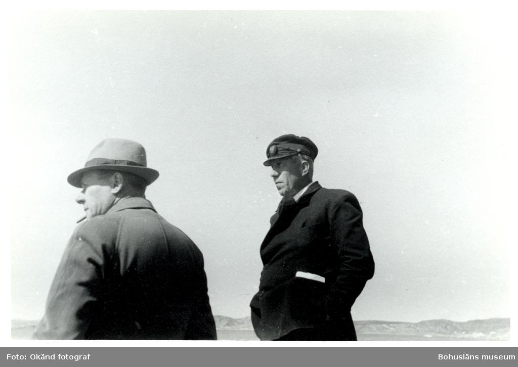 Två män står och blickar på något utanför bilden, det är starkt solljus