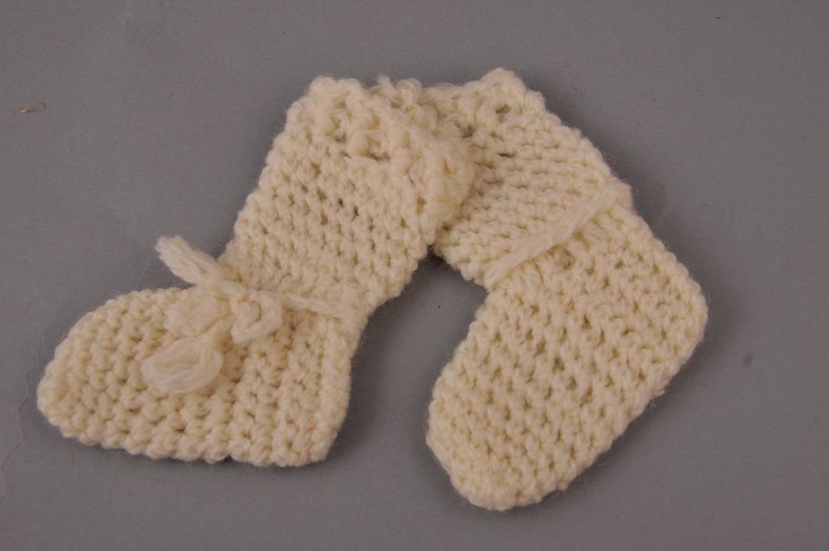 To babysokkar laga av kvitt laustvinna ullgarn. Ullsnor rundt vrist med sløyfe på eine sida.