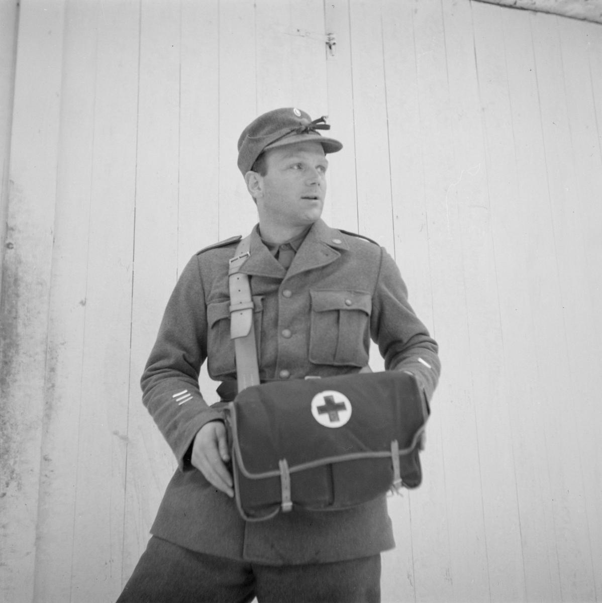 Porträtt av militär tillhörande Svenska frivilligkåren i Finland, F 19, står vid en husvägg. Mannen bär sjukvårdsväska.