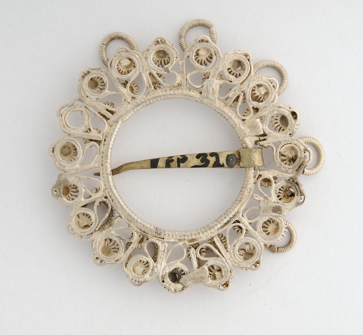 Sølje, krusesølje i sølv, ingen stempel. Gjennombrote filigransarbeid med krusar og 8 hemper med pålodda ringar. Tann  (nål) med litt dekor på.