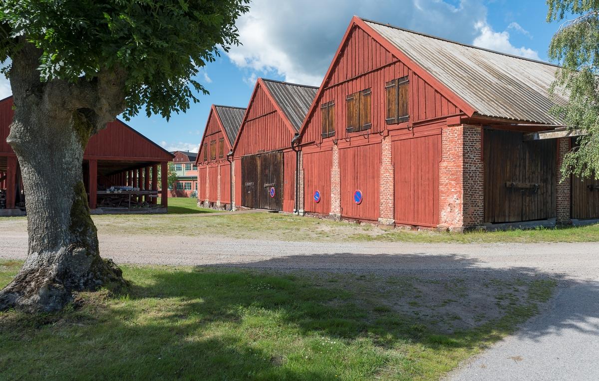 Fotodokumentation av byggnader på Lindholmen i Karlskrona. Till höger: Skjul för förvaring av ekvirke. Skjul 13, 14, 15. Dessa ritades av överstelöjtnant-mekanikus Jonas Lindströmer. Byggnaderna uppfördes omkring sekelskiftet 1800. Tll vänster: Slitaget byggdes omkring 1850 användes som ett virkesskjul. De runda träpelare ska ha varit utrangerade mastträn. Byggnaden är ca: 96 meter.