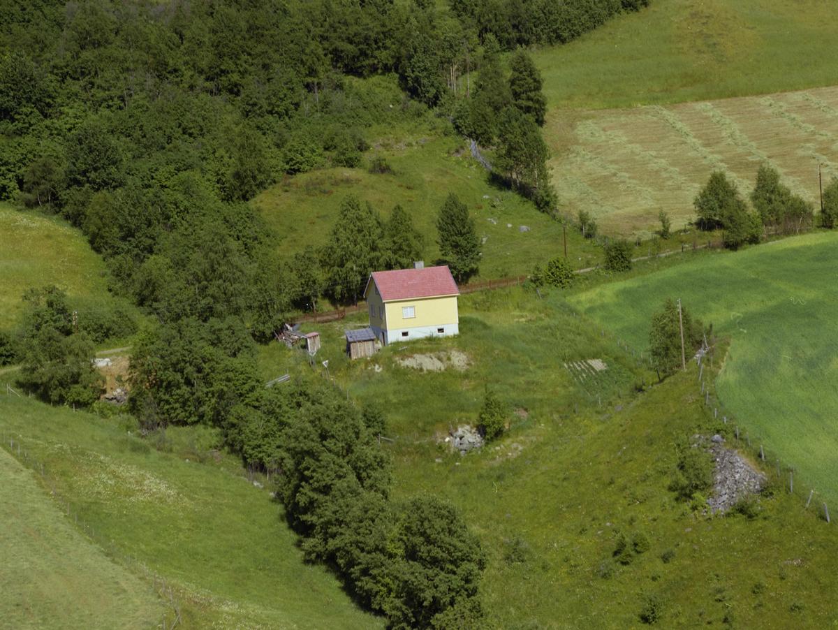 Sør-Fron, Hundorp, Øverbygda. Gult en og enhalvetasjes bolighus med rødt tak. Bygdeveg og skog, kulturlandskap.