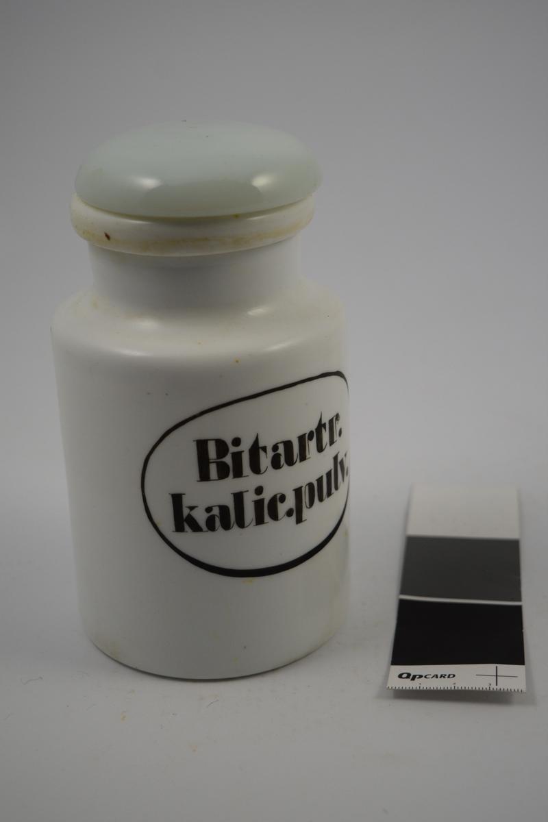 Hvit porselenskrukke med hvit propp. Påført etikett med svart oval kant og svart skrift. Denne type krukke ble brukt til oppbevaring av pulver. Krukken inneholder litt pulver. Pulveret ble brukt til produksjon av legemidler.