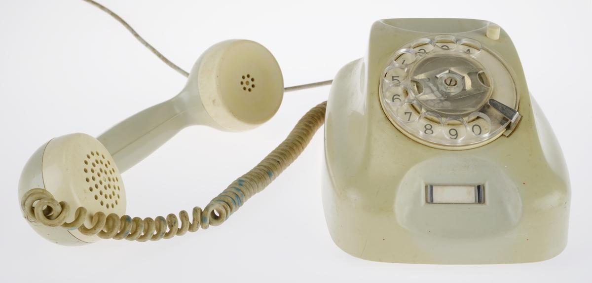Grå slitt telefon, grå fargen har blitt grå grønn. Røret har forskjellige merker etter bruk, hvite malingsflekker. Transparent tallskive med hvit bakgrunn og svarte tall. Har en hvit lapp under talerøret som det ikke står noe på. En del av ledningen mangler.