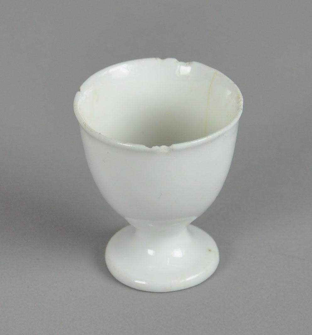 Eggeglass av glassert keramikk, med stett og utstående munningsrand. Det er endel hakk på munningsranden.