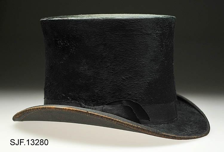 Flosshatt trukket med en filt av beverhår. Den er har en høy sylindrisk pull og en smal oppbrettet brem. Det er festet et svart hattebånd (sløyfe) på pullen. På toppen av pullen er det et lite hull, cirka 0, 8 cm i diameter. Hullet er dekket med en finmasket netting.  Trolig fungerer dette hullet som en slags lufting for den som bærer hatten.  Hatten bærer noe preg av slitasje, men sett i forhold til at den er over 110 år gammel er den i fint skikk. Svettebåndet inni hatten er løst. Inni hatten er varemerket plassert like ved luftehullet.  I og med at svettebåndet har løsnet, så avdekker det påtegninger med blyant som har ligget skjult under dette båndet. Kanskje er dette notater som er gjort under produksjon av hatten (registrator er usikker ).