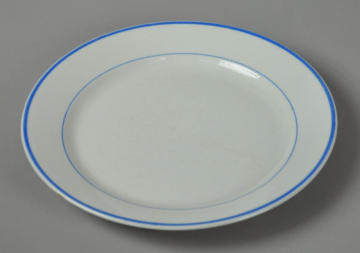Hvit tallerken av glassert keramikk, med to blå striper ved inner- og ytterkant på tallerkenen.