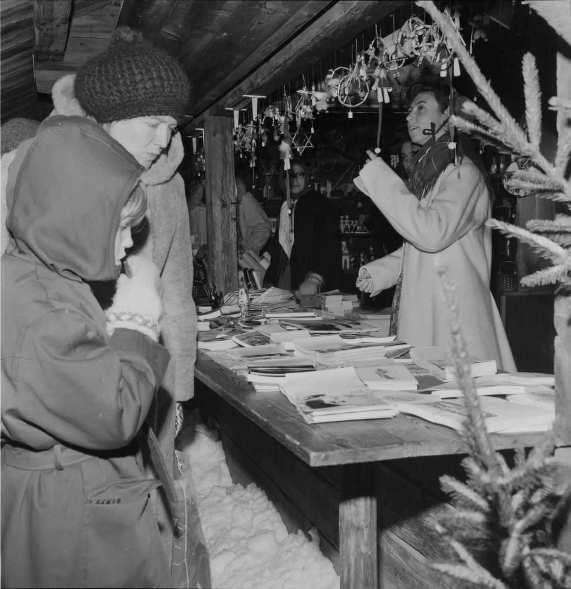 Julmarknad på Skansen. Personer tittar på varor i julmarknadsstånd. Halmslöjd. Kort. Gran.