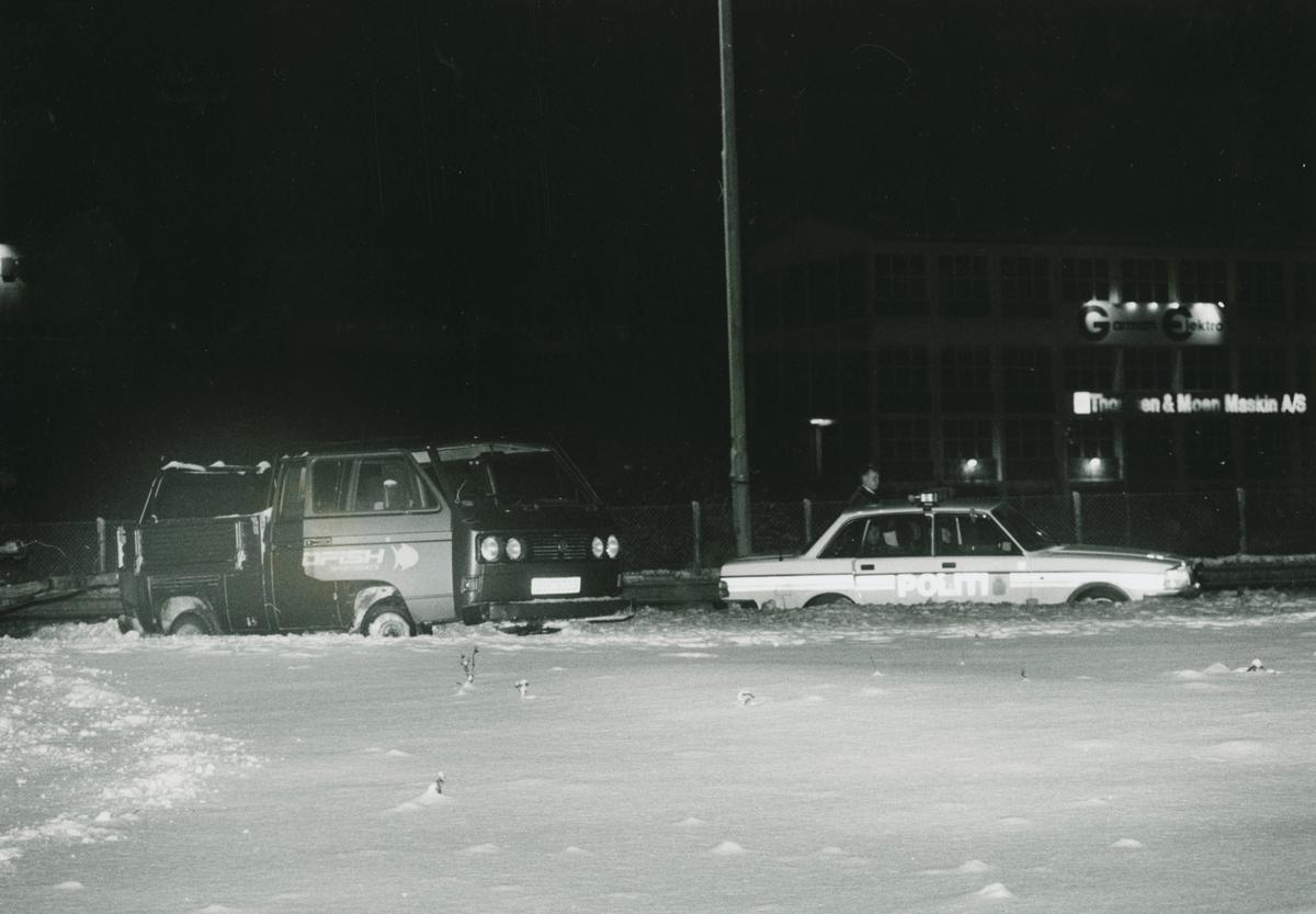 Pickuptruck og politibil i snø.