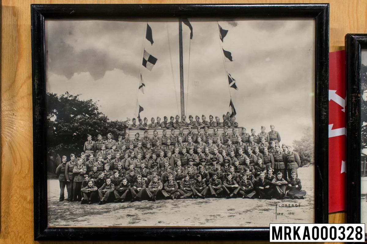 Fotografi taget på befäl och soldater som genomfört grundläggande soldatutbildning på 1:a Batteriet KA 2. Fotografiet taget utanför Signalskolan Gräsvik KA 2. Flobergs Foto 1942.