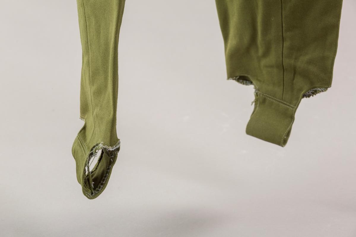 Grønn strekkbukse med stropper under bena. Avsmalnende ben. Glidelås i venstre side. Elastisk spennglidelås.