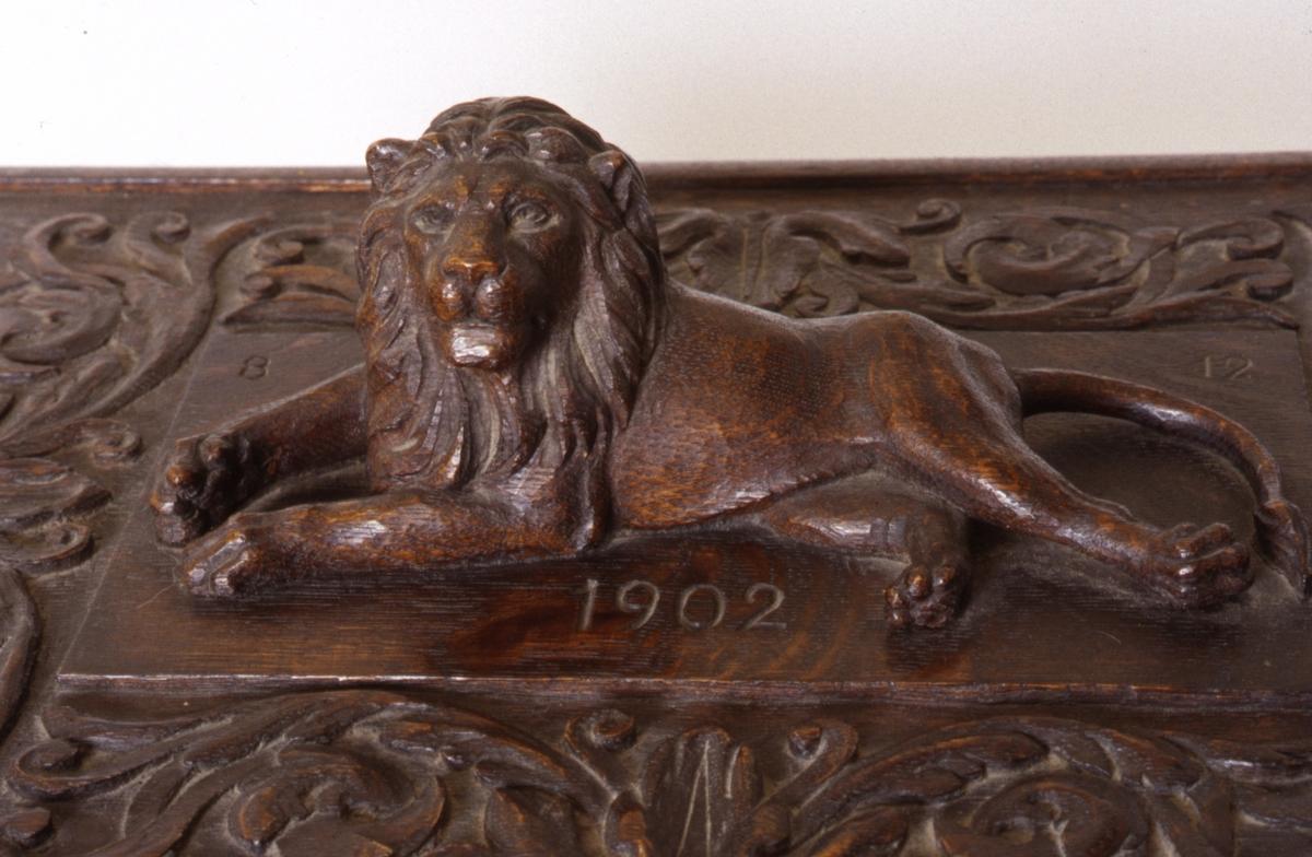 Skrin ei eik med lokk. Lokket har en bred akantusbord, og i midten en utskåret, opphøyd, hvilende løve. Skrinets kropp er tilbaketrukket med avrundede, søyleformede hjørner. Sidene har utskårne, opphøyde rosetter. Rund fotlist. Flate og sirkelformede ben.