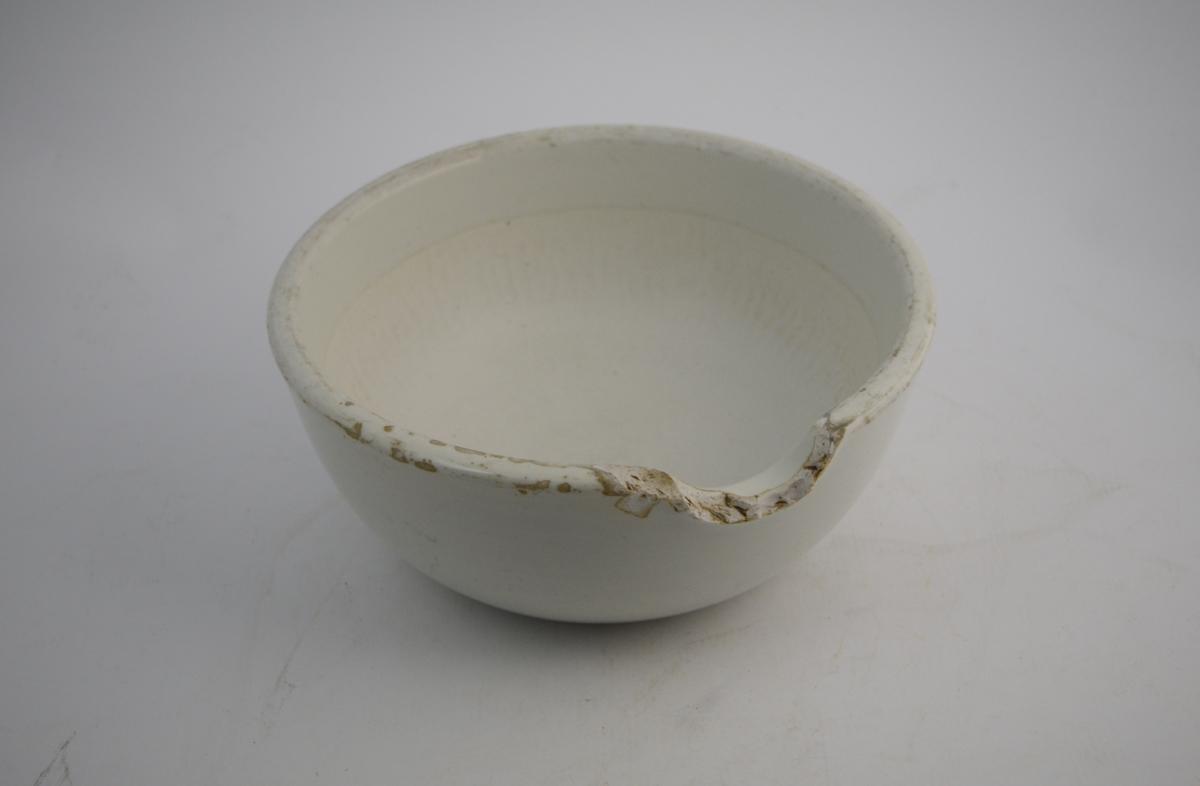 Porselensmorter, stor. Brukt til produksjon av salver, knusing av råvarer og urter, og blandinger av diverse stoffer. Brukes sammen med pistill (knuseredskap/røreredskap).