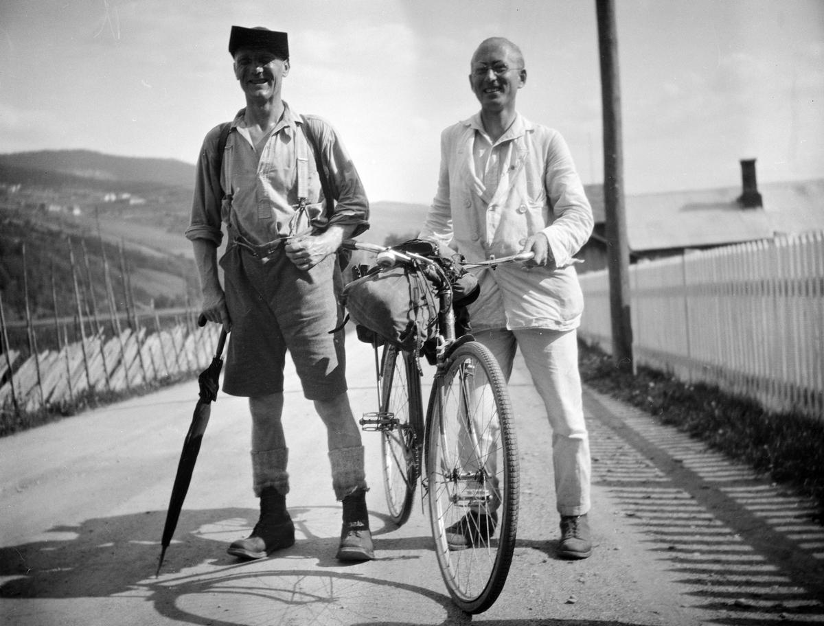 En mann med kortbukse og paraply og en med sykkel og lys dress står ute på vegen i Vålebru, Ringebu.