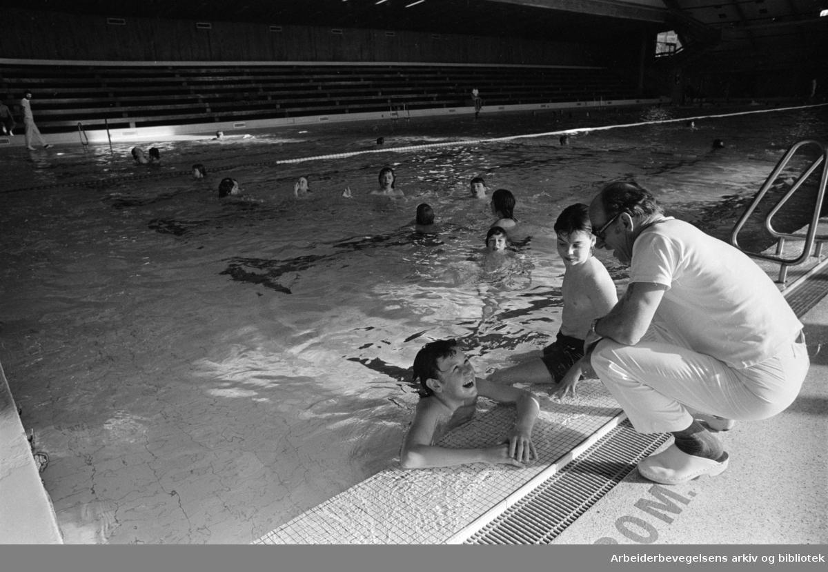 Tøyen. Tøyenbadet. Bademester Erling Jacobsen på bassengkanten. April 1976