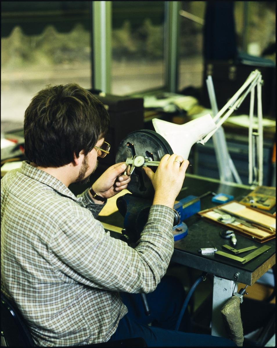 En mann måler og justerer på noen åpninger på en rundt skive ved et arbeidsbord på Hydro sitt aluminiumsverk på Karmøy.
