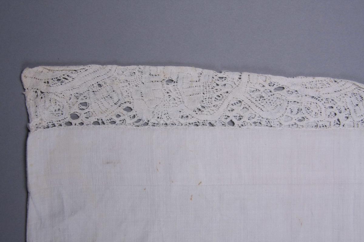 Hvit linlerret åpent i den ene kortsiden med smal fall og knytebånd. Den annen er sydd sammen med en 3 cm. bred knipling med stort rankemønster. Bred fall på begge sider av kniplingen.