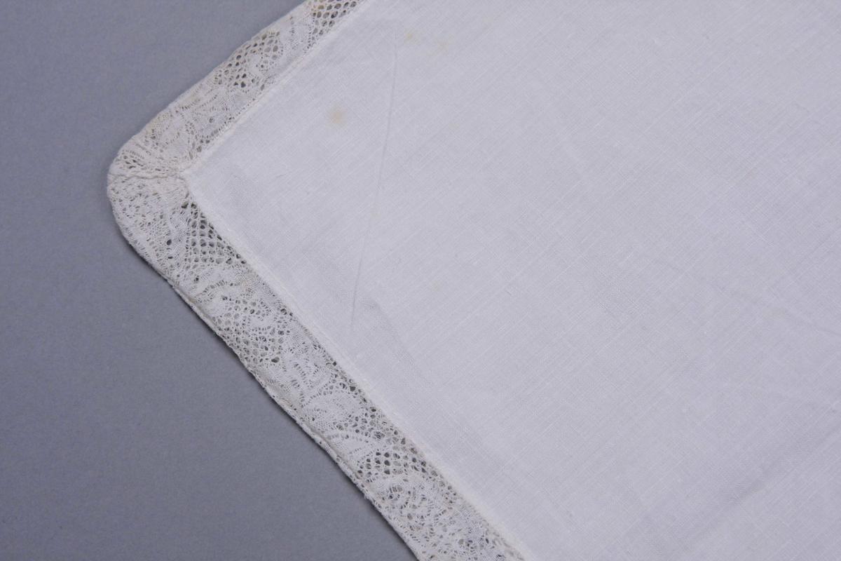 Hvit linlerret sydd sammen på tre sider med en 3,5 cm. bred knipling, meget fin med mønster av ren barokk blomsterranke. Smal fall på den fjerde siden.