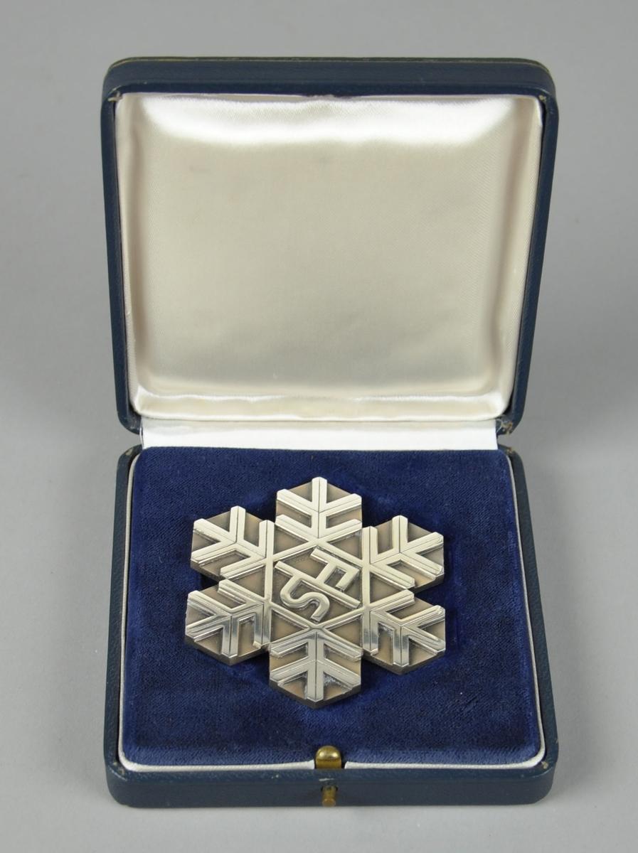 Sølvmedalje fra VM i langrenn i Squaw Valley 1960, formet og mønstret som et snøfnugg.  Medaljen ligger i et blått etui merket FIS