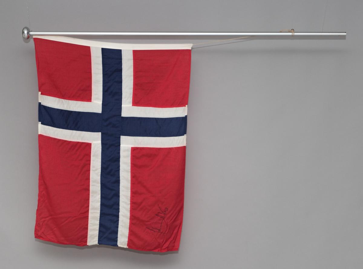 Norsk flagg med signatur av Johan Olav Koss. Flagget ligger en kartonghylse.