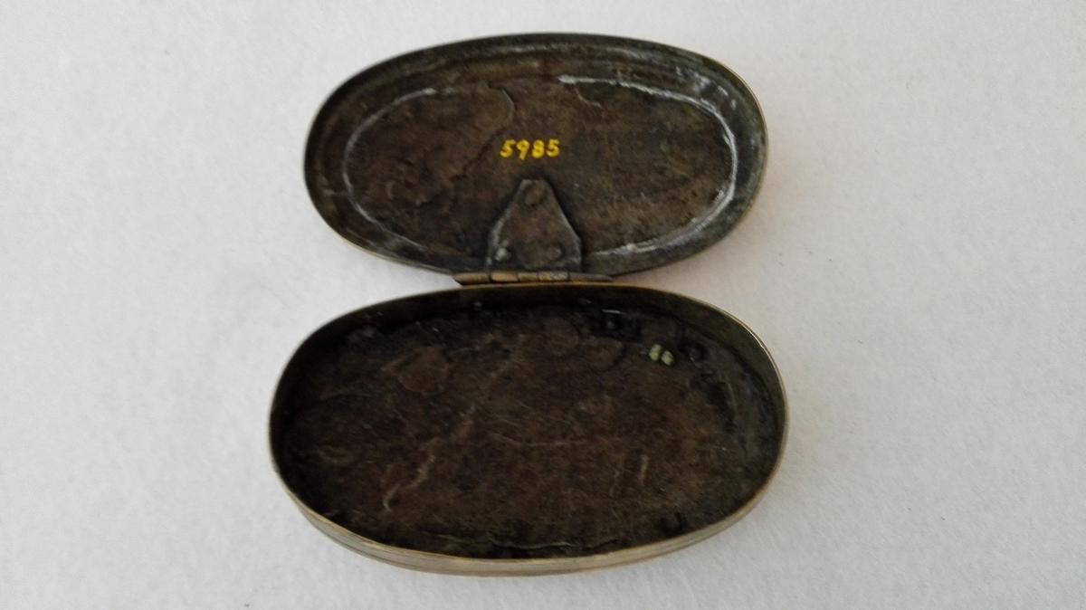 Form: Oval, flattrykt. 1 tobaksdaase av messing.  Oval, flattrykt tobaksdaase av messing. Paa laaget forsirt med indridsete strekornamenter og bokstaverne P.H.H. Gave fra Durdei Seim, Seimsdalen.
