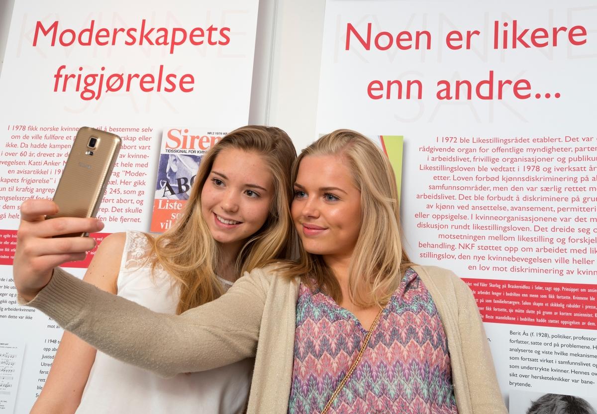 Kvinnemuseet, Kongsvinger museum, Hedmark. Jenter tar selfie med mobiltelefon i utstilling. Utstillinger. Ungdom. Besøkende. Publikum. Formidling.