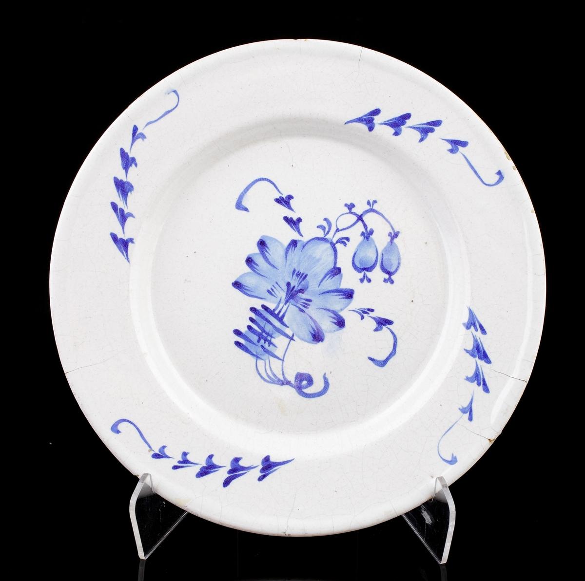 Tallrik i fajans. Blå handmålad dekor i form av s.k. humlemönster och kvistar. Saknar signering/stämplar. Trol. Marieberg.
