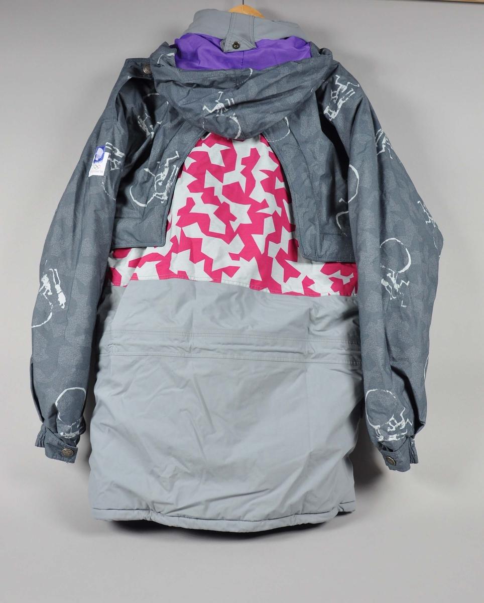 Grå og rosa jakke med krystallmønster. Krystallmønsteret inngikk i LOOCs designprogram. På jakken og jakkens knapper er det piktogrammer  fra de olympiske vinterleker på Lillehammer i 1994. Disse inngikk også i LOOCs designprogram. Det er påsydd et merke med logo for de olympiske vinterleker på Lillehammer i 1994. Jakken har hette som kan foldes inn i kragen. Størrelse L.