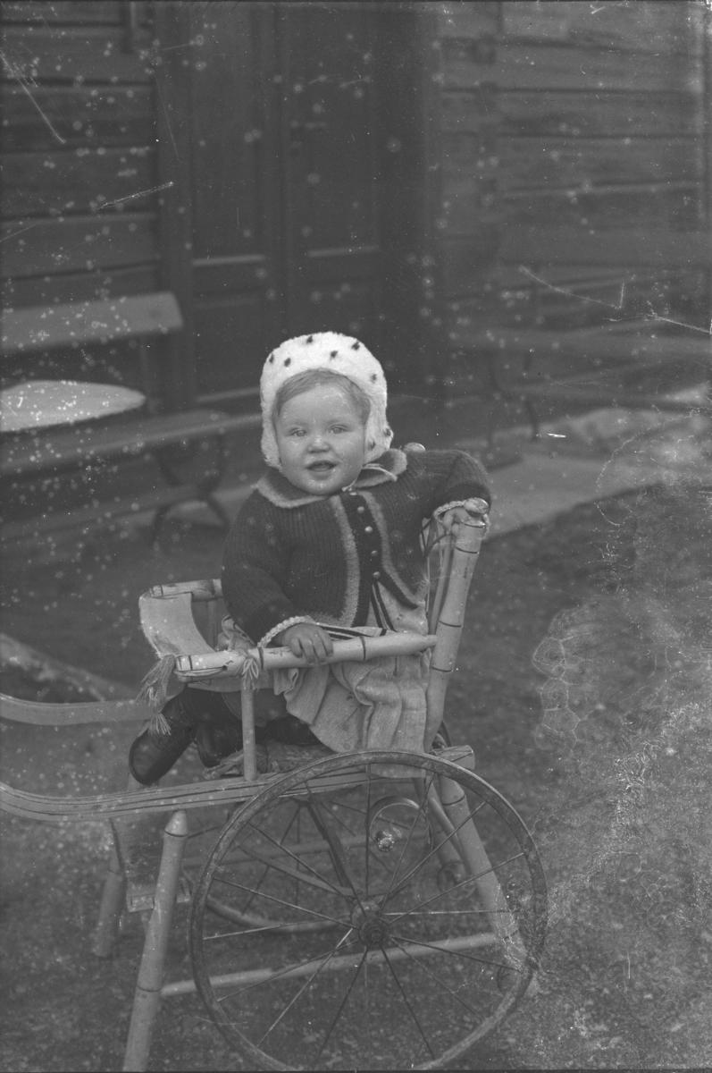 Liten jente sitter ute i kombinert barnestol og trille.