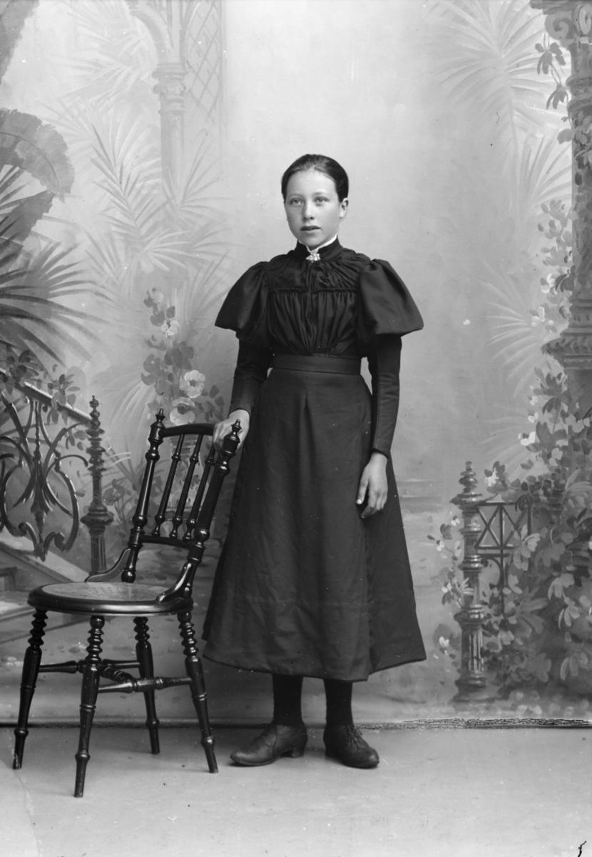 Portrett, ung jente står ved stol, helfigur.