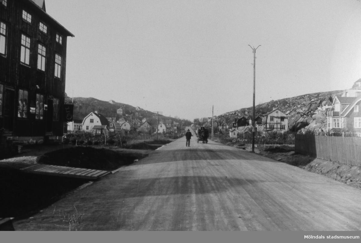 En hästskjuts och en fotgängare ses på Toltorpsgatan i Toltorpsdalen, Mölndal, före år 1923, då gatan stensattes. Stora huset till vänster låg ungefär där bensinstationen ligger idag. I huset fanns bl.a. Dalen bageri. Till höger kan man skönja Dalgångsgatan. T 3:35. Reprofotografi.