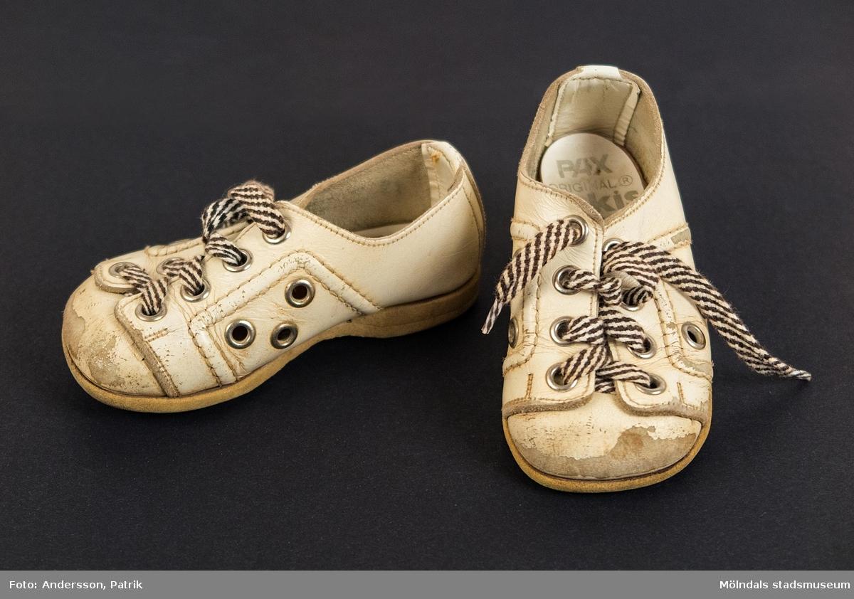 """1 par vita skor i storlek 21 tillverkade av Pax, 1978.  Skosnöret är blå och vit randigt.   Inuti skon finns stämpeln: """"PAX ORIGINAL Lekis ÅLDERBINDSULA"""", men är något slitet. I sulan finns storleken """"21"""" inristat."""