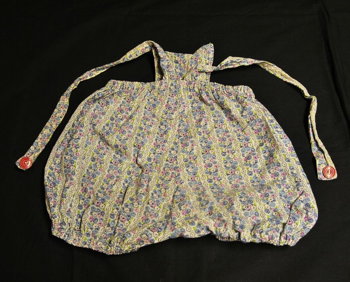 Rund form. Sommerbukse/-shorts med seler. Liten lomme foran. strikk i liv og rundt benene.