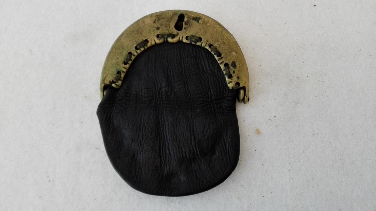 1 pung med messinglaas.  En lærpung med messinglaas forsirt paa kanten med indstemplete prik med cirkel om. Nökkel og fjer mangler. Bredde 8,5 cm.  Kjöpt av Lars Rosenlund, Leikanger