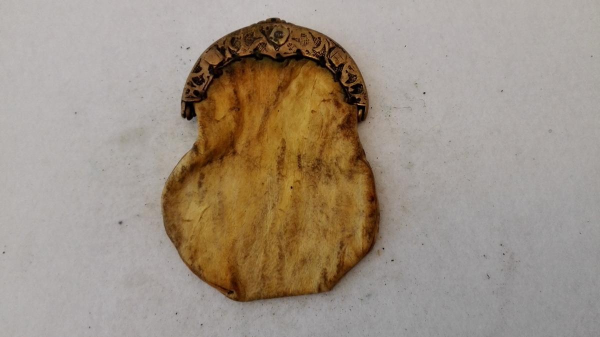 1 pung med messinglaas.  Liten pung av semsket skind. Messinglaaset har stöpte ornamenter. 1 rum. Disse tre gjenstande ( 7019-7020-7021 ), stammer fra Eri i Lærdal.  Kjöpt av landhandler Theodor Lindström, Lærdal.