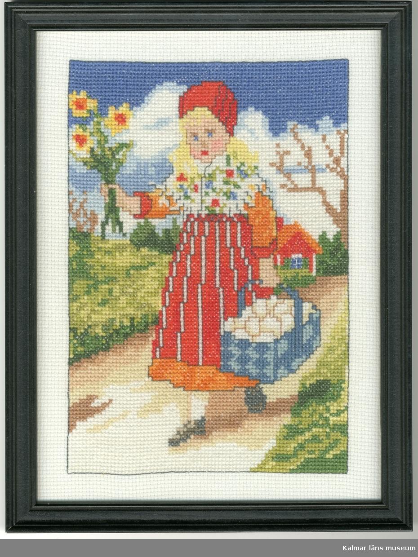 En flicka klädd i folkdräkt går på en väg. I ena handen bär hon en blå korg med vita ägg, i den andra håller hon tre påskliljor.