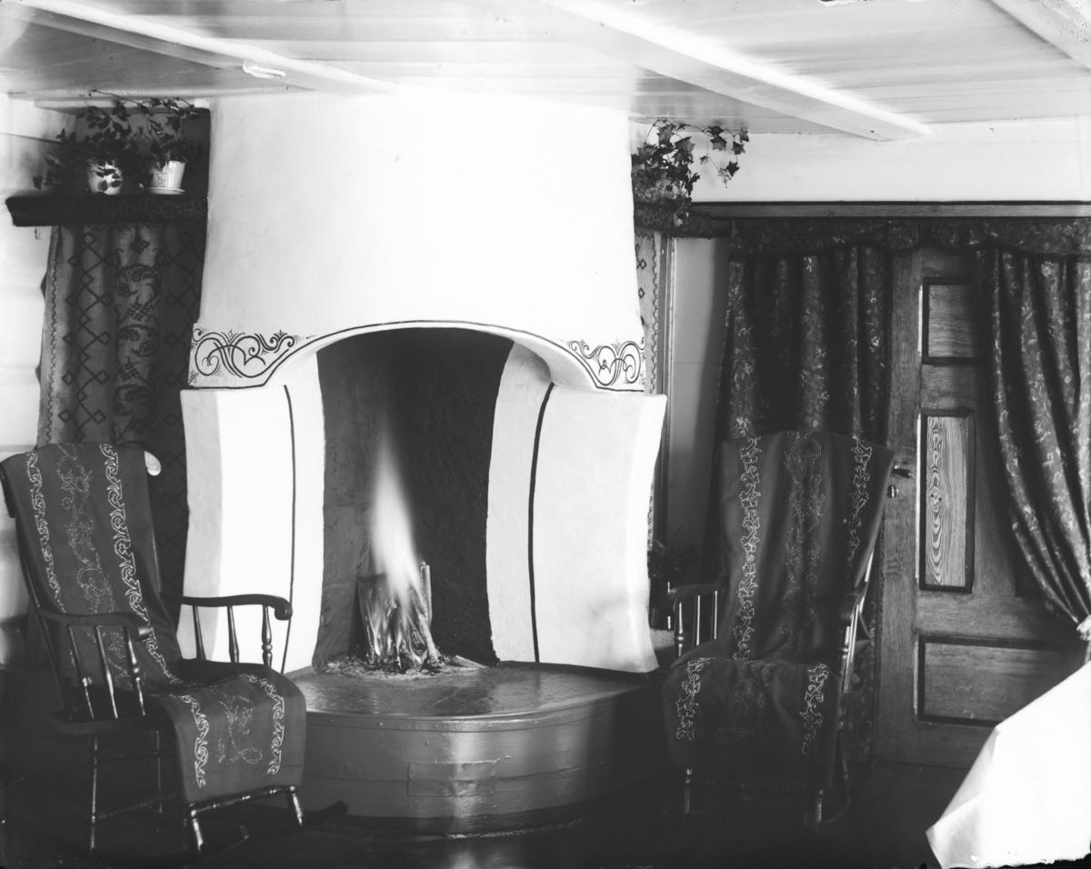 Stueflotten hotell og skysstasjon. Interiør fra peisstue med gynestoler og ild på peisen