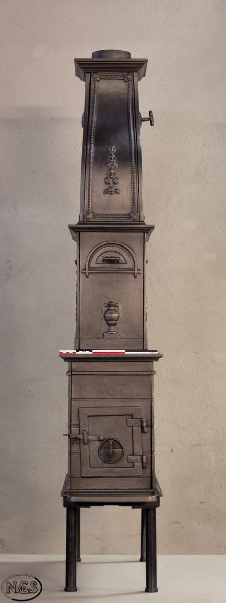 Etasjeovn - rektangulær i formen med ovnsluke på kortsiden.  På langsidene 1. etg liggende løve vendt mot venstre på sokkel i halvrunding.  Langside 2. etg firkantet åpning med ranker på sidene. På kortsidene NÆS i halvrunding med vase under. Ovnen avsluttes med en svunget topp med rundbuet åpning.