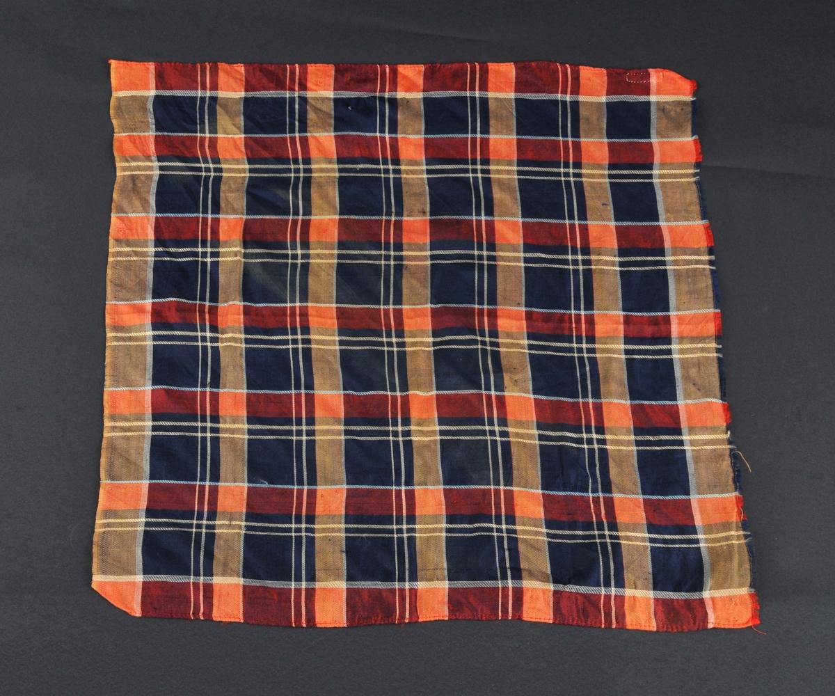 Silketørkle med rutemønster.To av sidene er falda, maskinsaum. Den tredje sida har jarekant, den fjerde er ikkje falda.