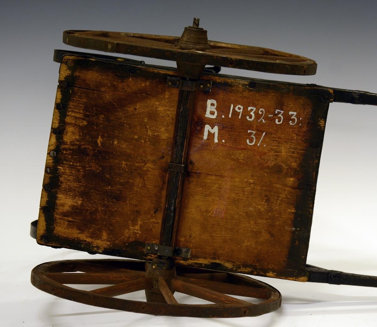 Trefigur: Hest med seletøy og kjerre med sete. Fra protokollen: Modell av hest, sele og skjusskjerre, arbeidd av Jon Sandviki, Raudland, truleg i 1870-aari. Hesten skori i tre, brunmaala. Selen med fullt massingstell. Kjerra av tre, jarna paa vanleg vis og med haage jarnfjørir paa baksætet (Innkomen restaurera).