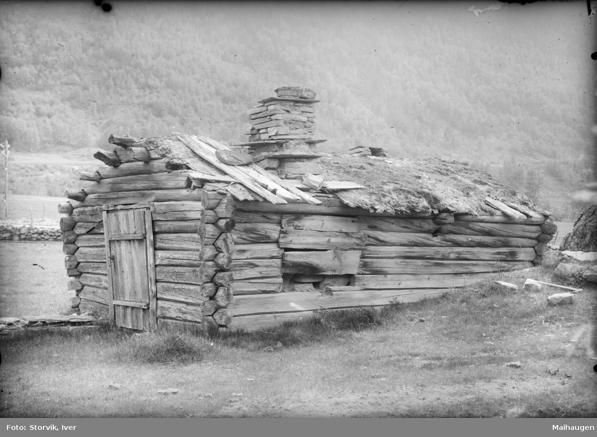 Gammelt lite tømmerhus med pipe i dårlig forfatning